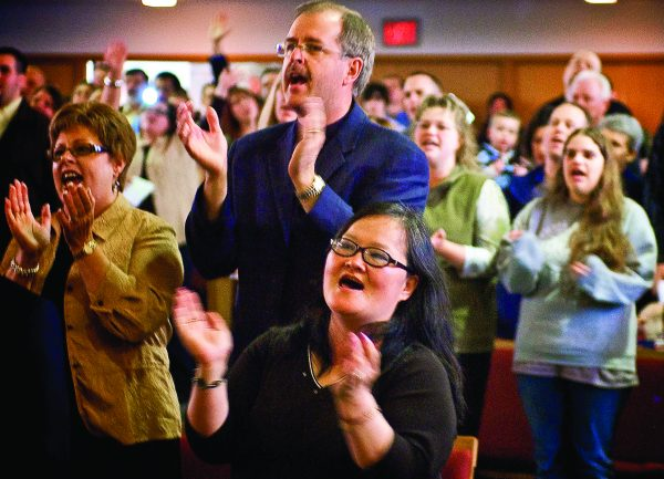 "Kerry and Karla Lowery, top left, clap during the closing chapel service at Cascade College. Kerry Lowery served on the Cascade Board of Governors. Shown in front is Lori Bird. The final chapel program included the singing of the alma mater, ""O Cascade,"" writen by John and Cynthia Fletcher."