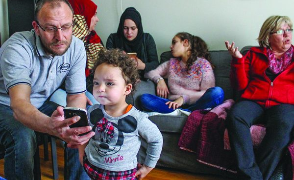 Momar Faham Katan shows his daughter Celine, 2, a picture. At right, in red, is Tintern church member Jori Warren.