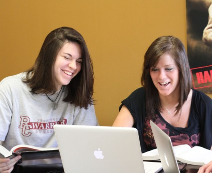 LIGHTER MOMENT : Rochester College students Liz Stockwell and Gabrielle Koerner laugh while working.  | PHOTO BY ELLIOT JONES