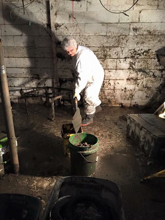 "A volunteer ""mucks"" out a basement in DeWitt"