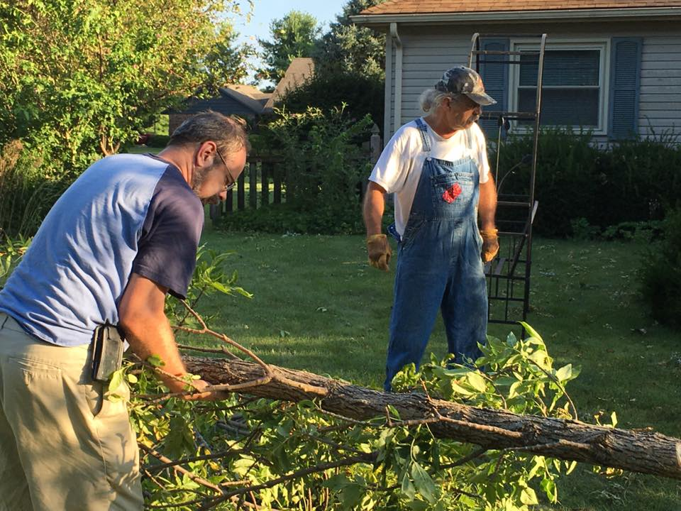 Church members clean up a tree that was knocked over when a tornado went through the town of Kokomo.