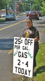 Church member Ann Marie Sarnak holds a sign advertising a ''Gas Buy Down'' event at a Gulf station in North Brunswick