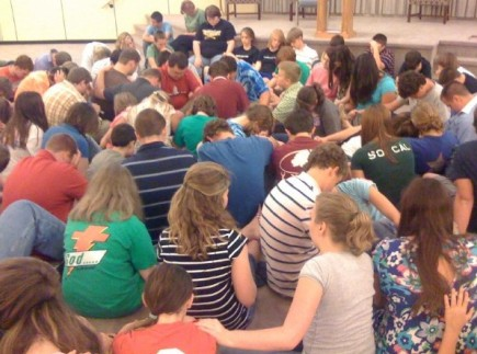 Campers at T.I.T.U.S. wrap their arms around each other as they pray during a late-night devotional. The weeklong session puts teens in pulpits and classrooms