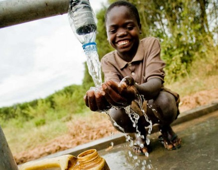 "A child in rural Rwanda experiences the feel of clean ""amazi"