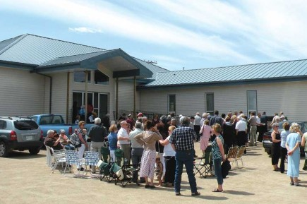 Members and visitors from the community dine on hot dogs and hamburgers at a fellowship meal celebrating the renovation of the Gravelbourg church building in south-central Saskatchewan. – PHOTO BY BOBBY ROSS JR.