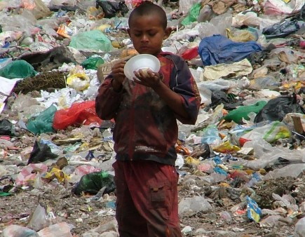 A child eats rice given to him by missionaries in a garbage dump near Tegucigalpa