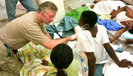 Dr. David Vanderpool of Mobile Medical Disaster Relief listens to the heartbeat of a Haitian victim of the Jan. 12 earthquake. Vanderpool