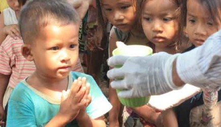 "A child says ""thank you"" for a snack before receiving it in a rural Cambodian village. Partners in Progress' nutrition program feeds about 1"