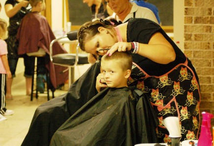 Tamara Lowery cuts kindergarten student Chandler Guske's hair at the recent Back2School BASH at the East Grand Church of Christ in Springfield