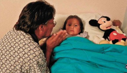 Norman Chee Atchison prays with 3-year-old Monica before she goes to sleep at Manuelito Navajo Children's Home in Gallup