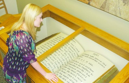 Gracie Gibson views what is described as the world's largest Bible. The King James Bible measures 43.5 inches tall by 98 inches wide. It is housed at the Abilene Christian University library in Texas. – PHOTO BY GRANT RAMPY