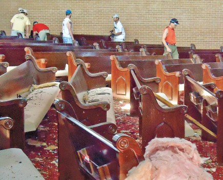 Members survey tornado damage inside the Central Church of Christ auditorium. Some gather songbooks and begin removing pews. – PHOTO BY JEREMY D. SMITH