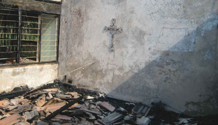 A metal cross remains on the wall in the ruins of the Sheros' home. – WWW.MBALEMISSIONTEAM.COM