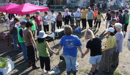 Volunteers pray before hosting a cookout in Ishinomaki