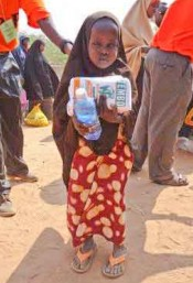 A girl in the Dadaab refugee camp in Kenya holds food and water provided by workers with Christian Relief Fund. – PHOTO PROVIDED