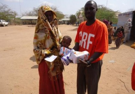 A worker representing Children's Relief Fund gives food to a woman and her child in the Dadaab refugee camp in Kenya. – PHOTO PROVIDED
