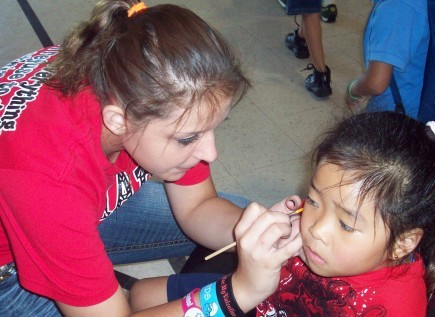 Church member Rebekah Hall paints a child's face during the recent seventh annual Back to School Roundup at the Alameda Church of Christ in Norman