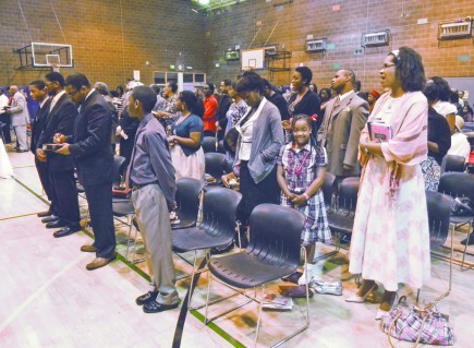 Members and visitors stand to pray during a Sunday service by the Holgate Church of Christ in Seattle. A community center's gymnasium serves as the congregation's temporary Sunday morning home. – PHOTO BY BOBBY ROSS JR.