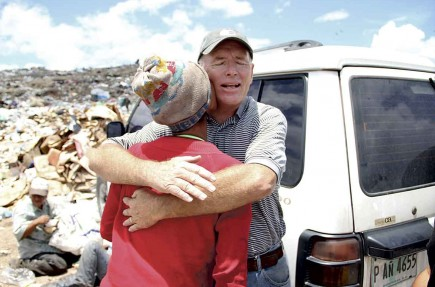 Marc Tindall hugs a woman at the Honduras garbage dump where he helps feed the poor. – PHOTO BY TREY MORGAN