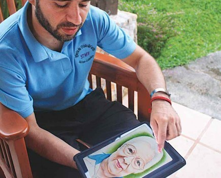 Roy Leandro uses his iPad to show portraits he painted. The church member hopes one day to use his talents to help the needy in Africa. – PHOTO BY ERIK TRYGGESTAD