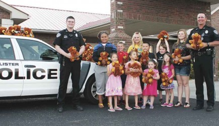Police officers Randall Hey and Jeff Loberg accept a donation of 250 teddy bears from children at the Hollister Church of Christ in Missouri. Through the 'Bear Hugs Project