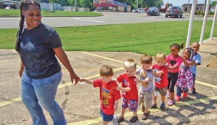 Follow the leader - Toddlers practice their train formation as they follow Vacation Bible School teacher Sesha Ledbetter from snacks to games. A recent VBS