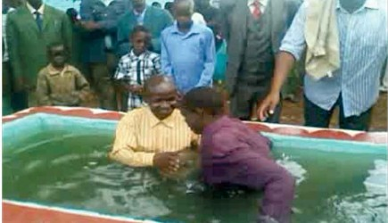 Isamel Sang baptizes a new believer near the Kericho prison. – PHOTO PROVIDED