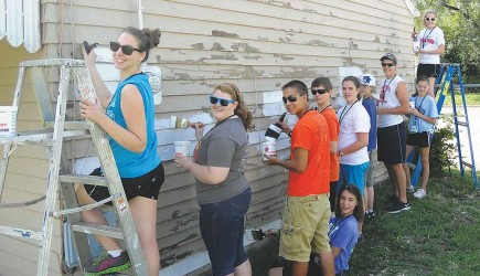 Some of the 226 volunteers from four states who participated in the Wichita Workcamp scrape and repaint a Kansas home. The Northside Church of Christ hosted the service camp. – PHOTO PROVIDED BY MARK YEAKLEY