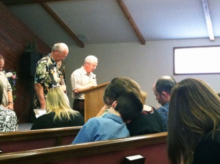 Southeast Church of Christ elders lead a prayer Sunday for the victims of the Aurora