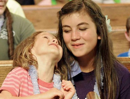 Jordyn Swoger cozies up to Emily Herring during Vacation Bible School at the Elkhorn Church of Christ in Wisconsin. – PHOTO BY JIM FROST