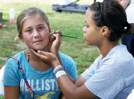 Brittany Brit paints the face of Jasmine Payne during a community outreach event by the Hayesville Church of Christ in North Carolina. The 35-member congregation organized a free car wash and other activities designed to open doors to sharing the Gospel