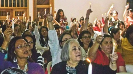 Women from South America hold up candles during a retreat and conference hosted by church members in Medellin