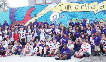 Football players and cheerleaders from Fort Worth Christian School in Texas make friends at the Fortress Youth Development Center
