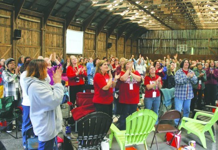 New England church members offer a standing ovation to the men who cooked and cleaned during the fall women's retreat at Gander Brook Christian Camp in Raymond