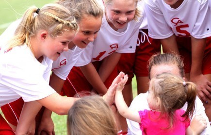 Gabbi Cook gives a high-five to junior high soccer players at Columbia Academy