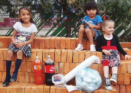 Smiling girls sit on stacks of bricks destined to become the meeting place of the La Libertad Church of Christ in the central Mexican city of Leon. Members of the Coldwater Church of Christ in Michigan worked alongside missionary Ben Baker