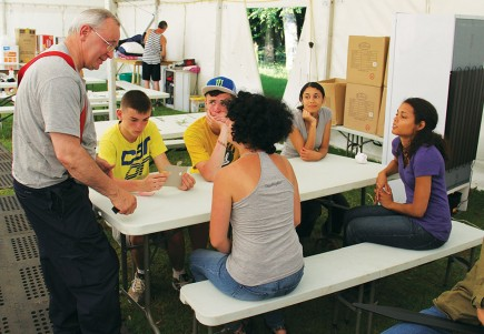 Bert Ritchie talks to counselors and cooks during a break at Camp Shamrock. The Irish-born preacher says that serving at the camp is a highlight of his 40-plus years in ministry. (PHOTO BY ERIK TRYGGESTAD)