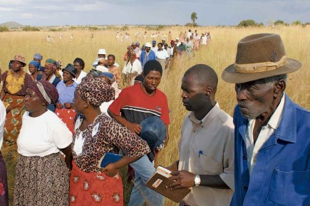 Mourners walk through a field to a graveside service in rural Zimbabwe. The deceased
