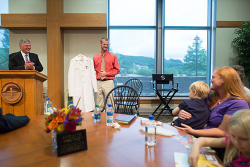 Dr. Kent Brantly receives a new medical coat during a visit to Samaritan's Purse headquarters in North Carolina.