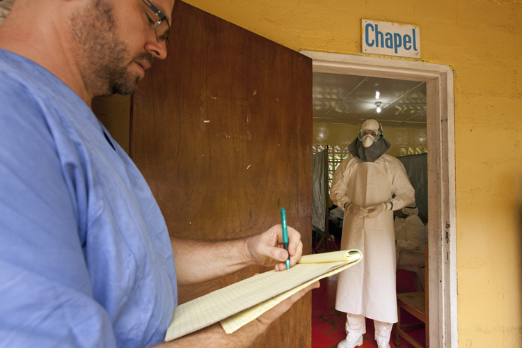 Dr. Kent Brantly gives orders for medication to administer to the Ebola patients through the doorway of the isolation unit. Brantly spent almost four hours in the Tyvek suit in order to care for the three patients in the unit.