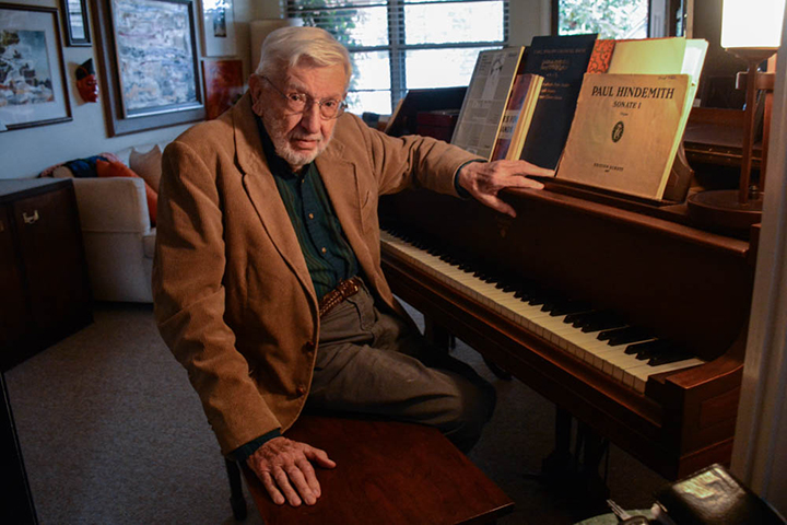 Harold Fletcher sits at his home piano. He retired on Dec. 4
