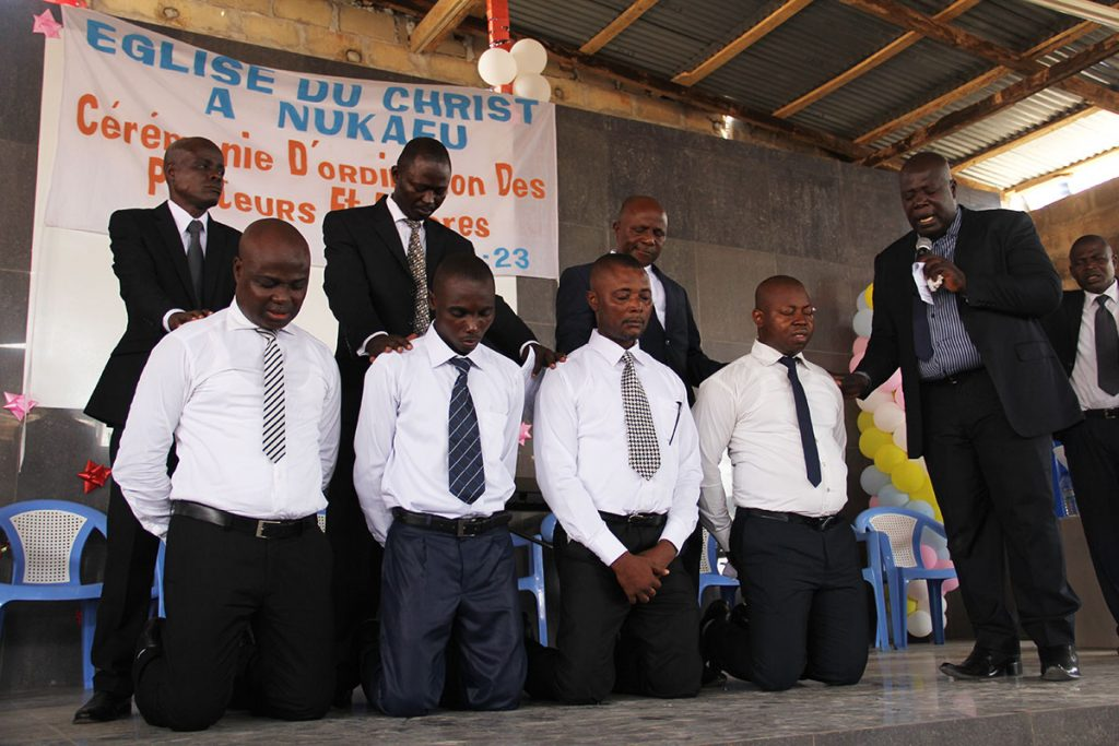 Agbessy Komi prays — alongside his three fellow