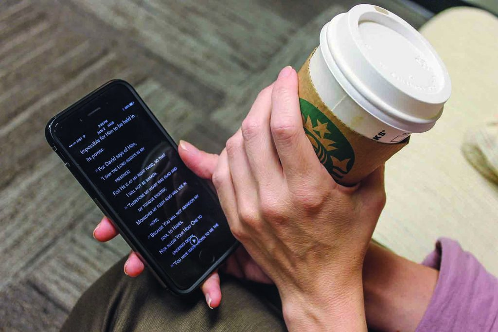 A modern-day Christian reads the Bible on a smartphone.