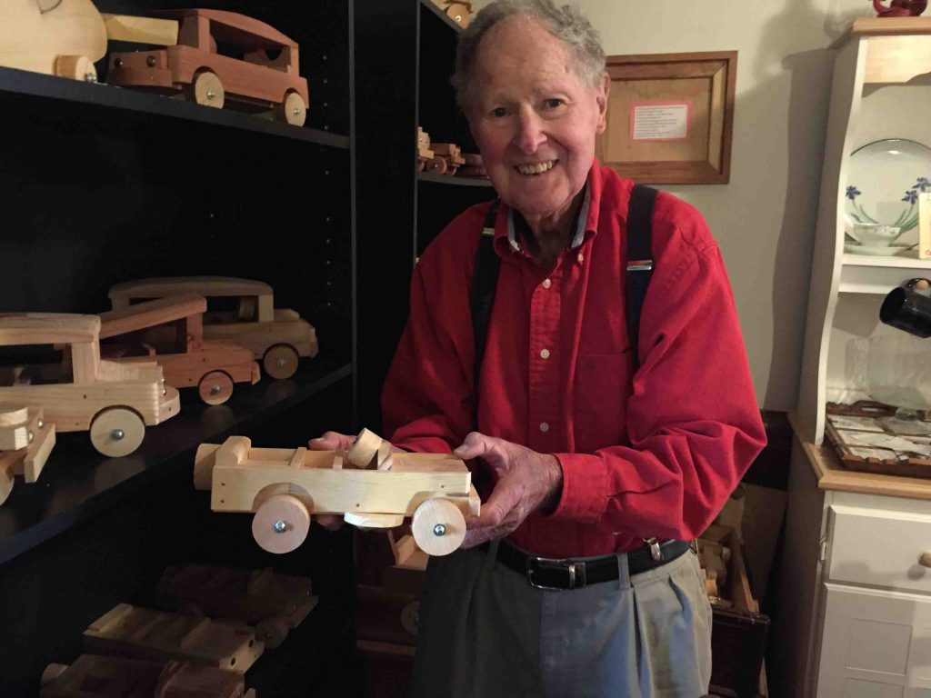 Ernest Raines shows off one of the toy cars he built.