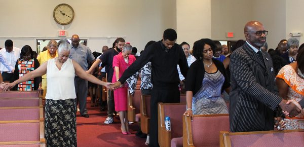 Members of the Oakland Church of Christ in Southfield, Mich., hold hands as they pray for racial reconciliation at the 50th anniversary of the Detroit riot in 2017.