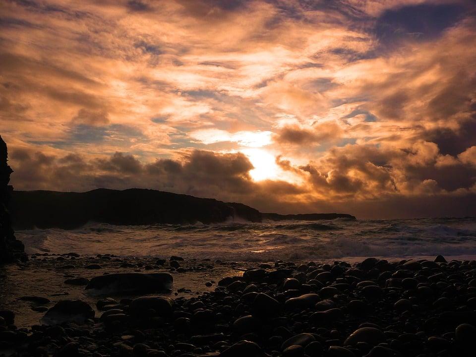 Waves crash along the coast in Ireland at sunset.