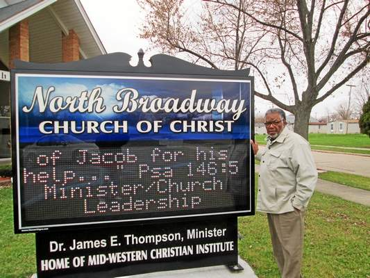 James Thompson stands next to the North Broadway Church of Christ's sign in Mount Clemens