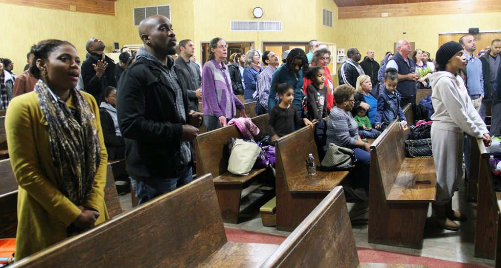 Members of the Long Island Church of Christ sing during a Friday night devotional. (PHOTO BY ERIK TRYGGESTAD)