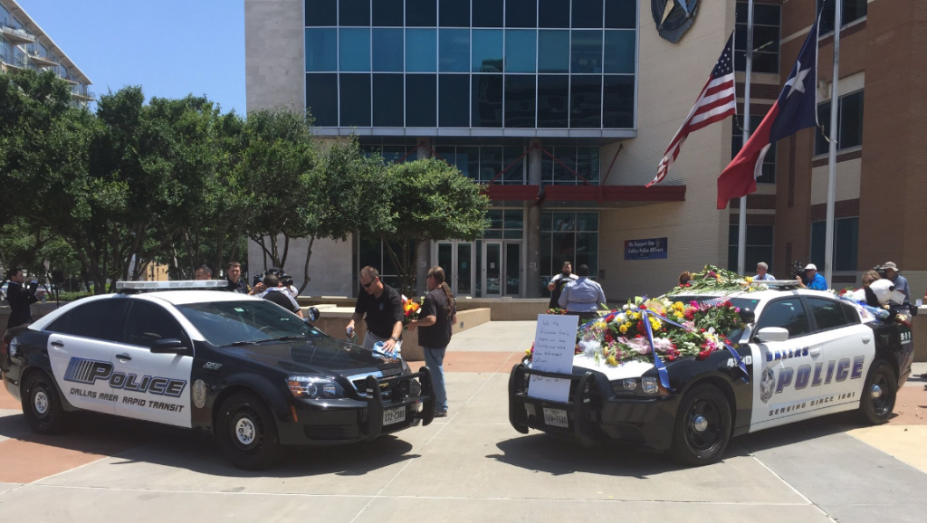 Two squad cars have been set up as a memorial in front of the Dallas Police Department headquarters.