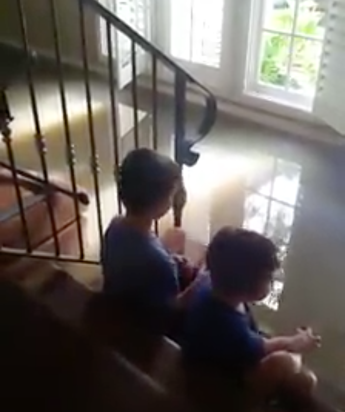 Two young boys sit on the stairs in their home as flood waters slowly fill the first floor.